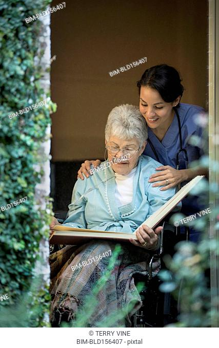 Nurse looking at photo album with woman in wheelchair