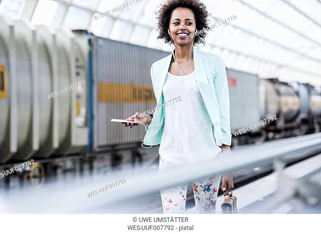 Portrait of smiling young woman with earphones and smartphone at platform