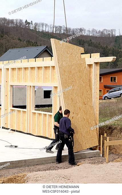 Europe, Germany, Rhineland Palantinate, Men installing and fixing wooden walls of prefabricated house