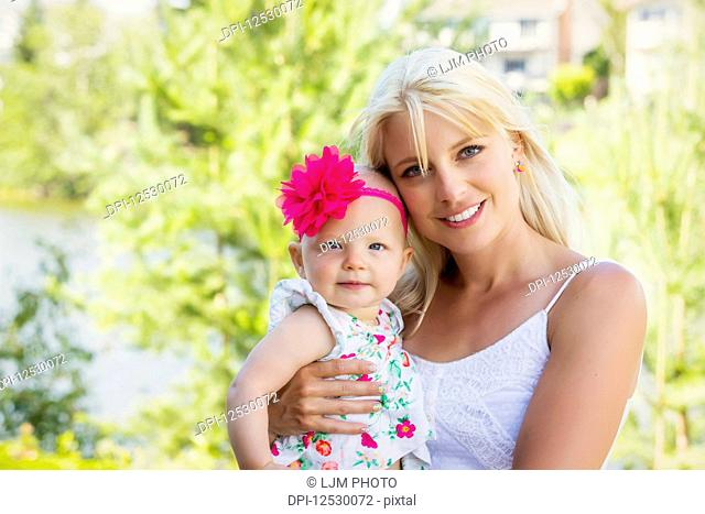 A beautiful young mother with long blonde hair enjoying quality time with her cute baby daughter in a city park on a summer day and posing for the camera;...