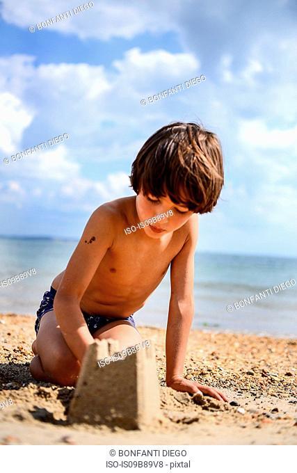 Boy making sandcastle on beach