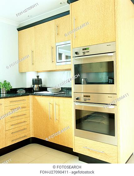 Eye-level double oven in modern kitchen with pale wood unit