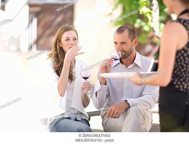 Waitress with tray and couple sitting outdoors tasting red wine