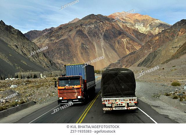 Two heavy trucks, going in opposite direction, pass each other in the high Andes near the border of Chile and Argentina