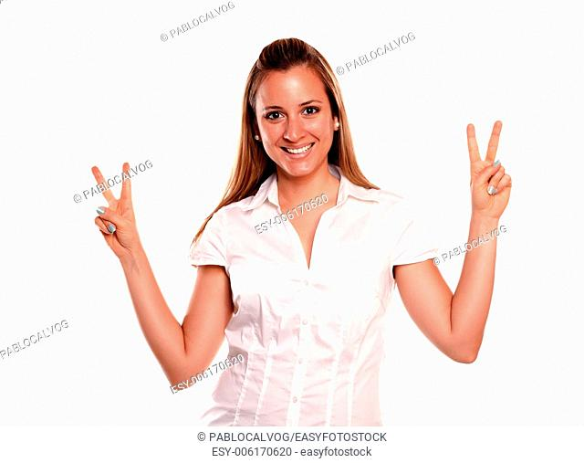 Friendly young female with a winning attitude looking at you against white background