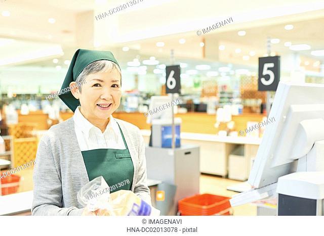 Senior woman cashier in supermarket