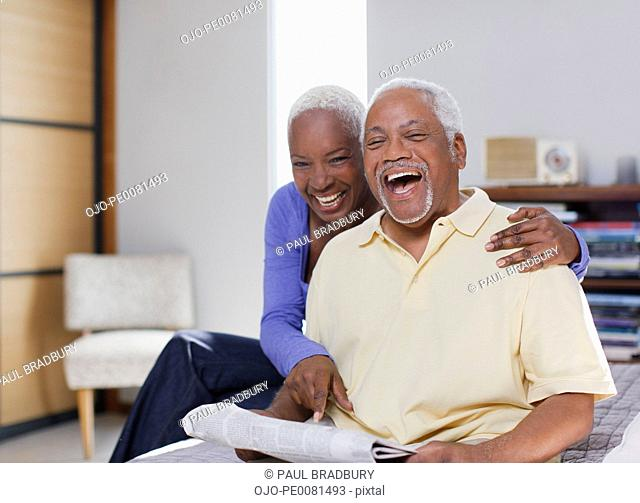 Older couple laughing together indoors