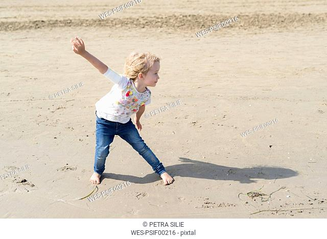 Playful little girl posing on the beach