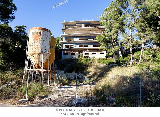 abandoned building site with incomplete build and above ground storage tanks