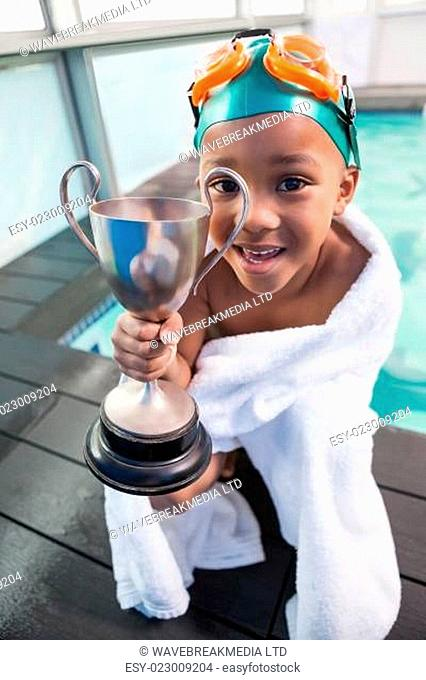 Cute little boy wrapped in towel with trophy poolside