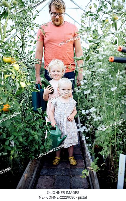 Father with daughters in greenhouse