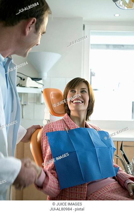 Woman in dentists chair shaking dentists hand