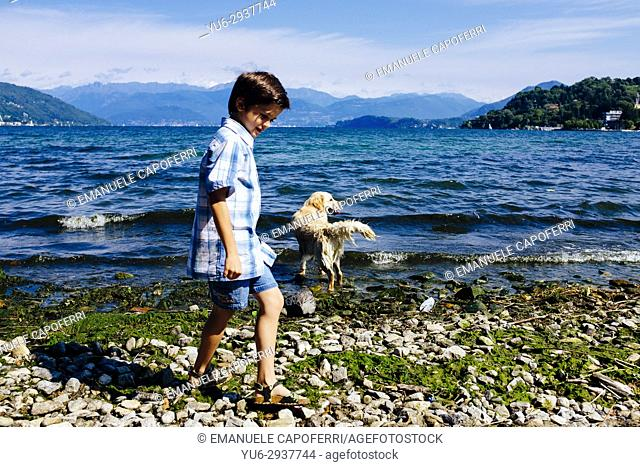 baby plays with her dog at the lake, Lake Maggiore, Italy