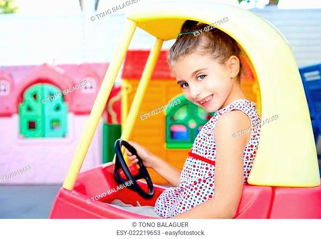 children girl driving a toy car