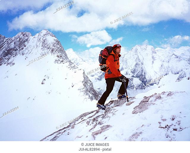 Hiker climbing up snowy mountain