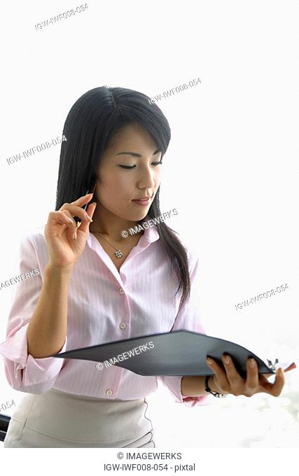A woman holding a file and a pen lost in her thoughts