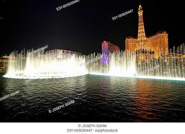 Bellagio Casino Water Show at night with Paris Casino and Eiffel Tower, Las Vegas, NV