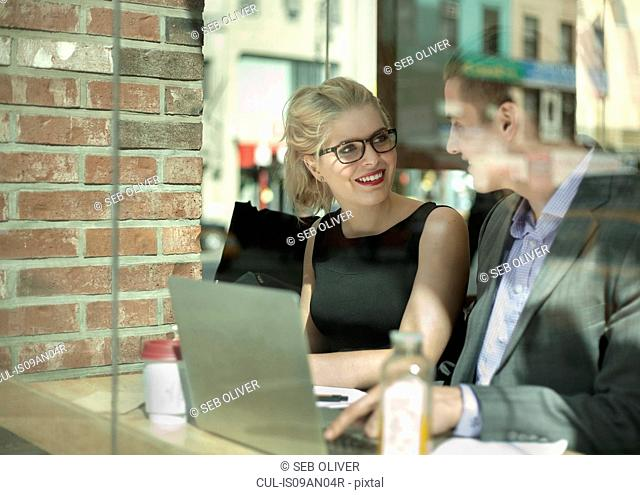 Young businessman and woman chatting in cafe, New York City, USA