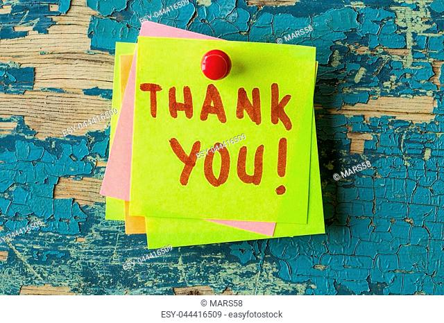 Thank You text written on sticky note on rustic wooden background. Motivational quotes