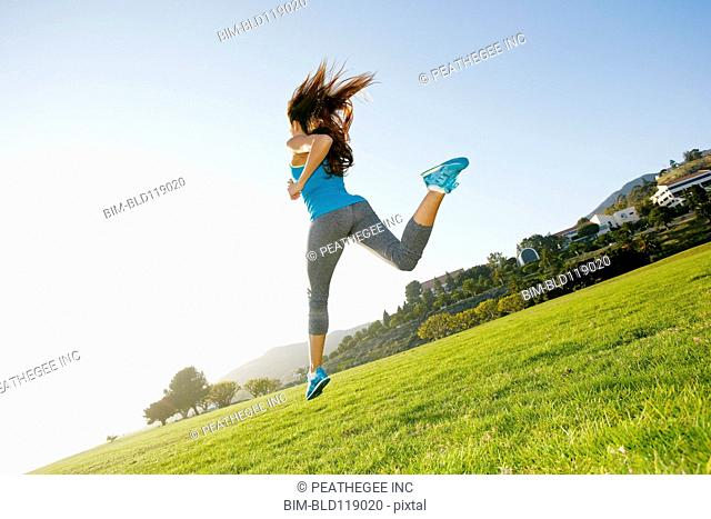Mixed race woman running in park
