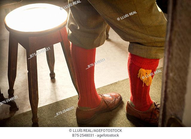 Close up of the legs of a man dressed in hunting garb, with baggy pants in Prince of Wales fabric, red wool socks with pom pom, Oxford style leather shoes