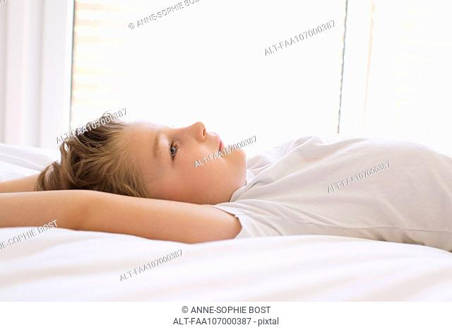 Boy relaxing on bed