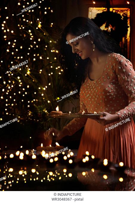 Young woman arranging oil lamps at a diwali festival