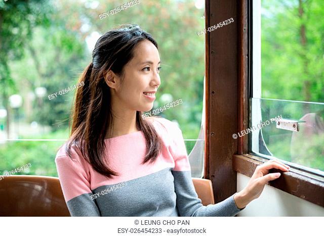 Woman looks out the window of tram