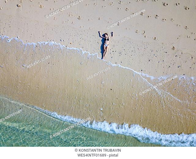 Indonesia, Bali, Melasti, Aerial view of Karma Kandara beach, woman lying on beach