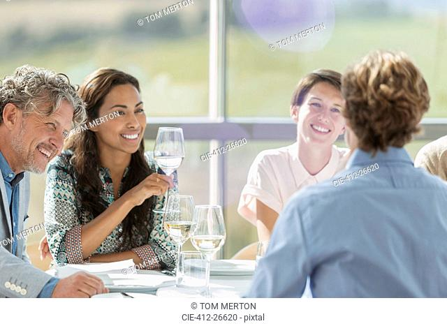 Friends drinking wine and talking at restaurant table