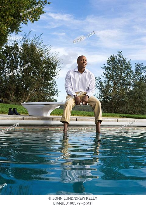 African American man sitting on diving board