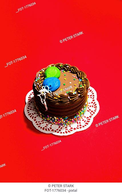 Still life chocolate birthday cake on vibrant red background