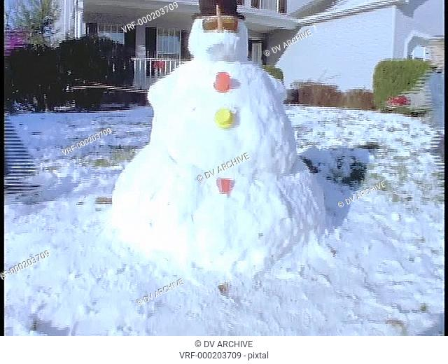 Children stand next to a snowman in front of their house