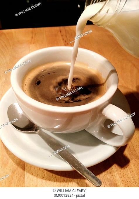Milk being poured into a cup of black coffee