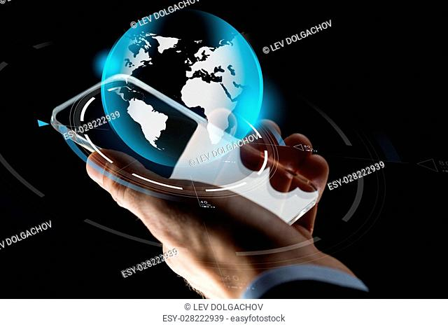 business, mass media, people and future technology concept - close up of businessman hand with transparent smartphone and virtual earth hologram over black...