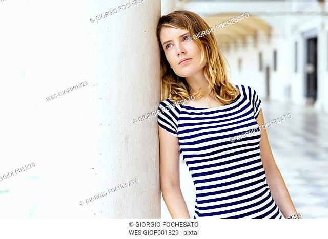 Italy, blond young woman leaning against column