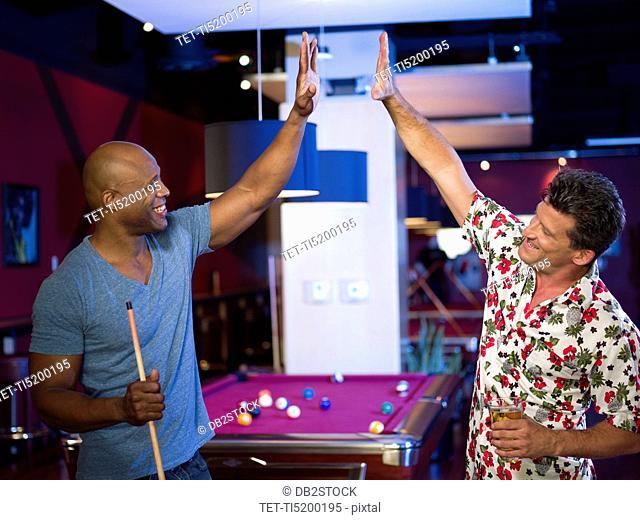 Men enjoying game of pool at bar
