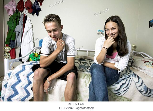 Teenage Boy and Girl Sitting on Bed
