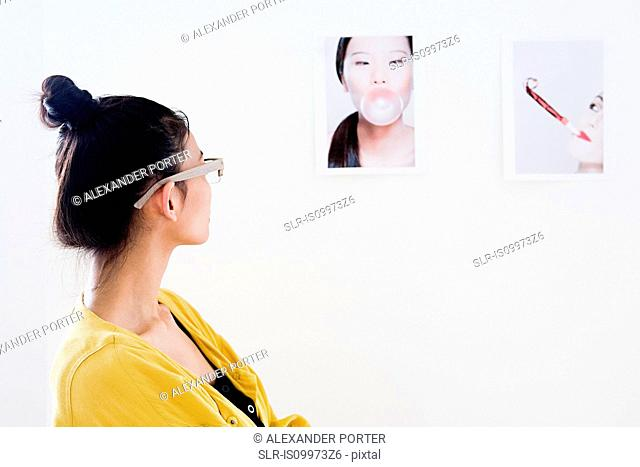 Young female fashion designer looking at photographs on white wall