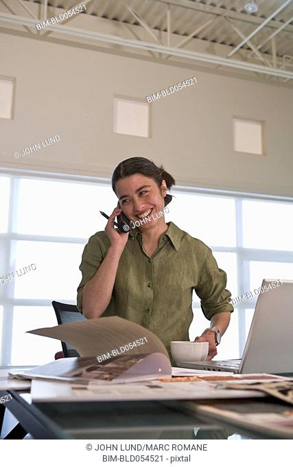 Mixed Race businesswoman talking on telephone