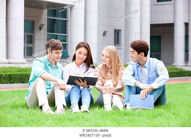 Domestic students and internationals students in college seated on a grass looking at a book together on campus