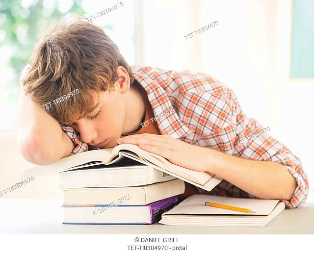 Teenage boy (14-15) sleeping in classroom