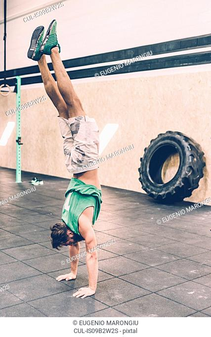 Young male cross trainer doing handstand in gym