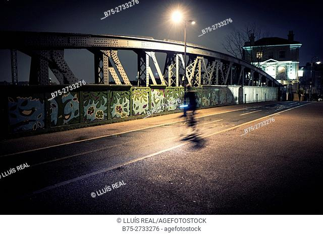 Iron bridge and biker, with street lamp. Blurred motion. Regent's Park Rd. London, England
