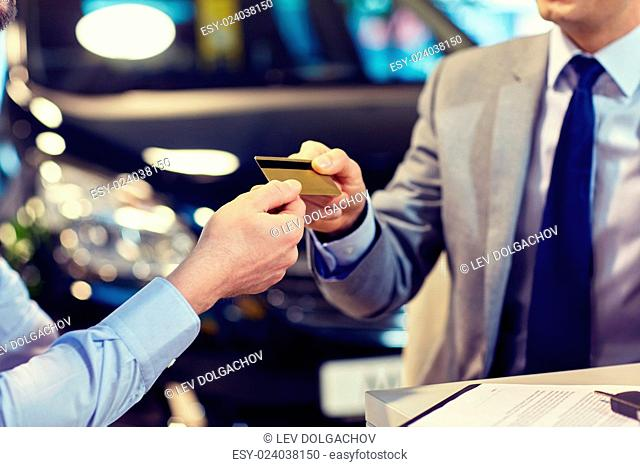 auto business, sale and people concept - close up of customer giving credit card to car dealer in auto show or salon