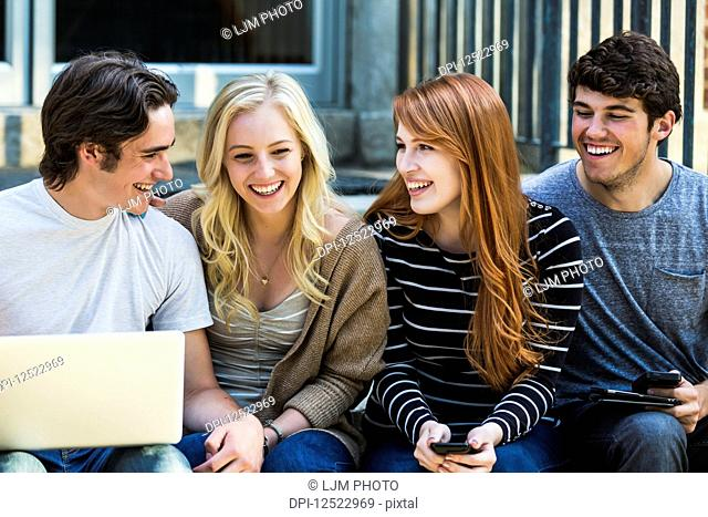Four students sitting in a row on a step using their technology on the university campus and laughing about something funny; Edmonton, Alberta, Canada