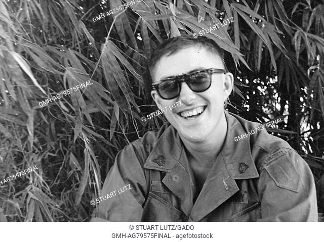 A United States Army serviceman wearing his utility fatigue shirt and sunglasses, he is sitting in front of some tall tropical foliage and smiling, Vietnam