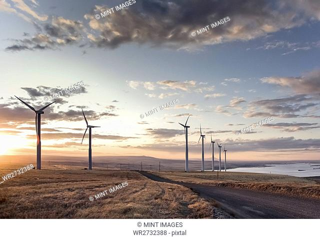 A group of wind turbines standing next to a road in a moorland landscape on the coast at dawn