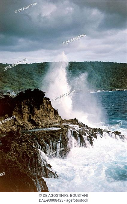 Waves crashing against the eroded volcanic cliffs of Christmas Island, Australia