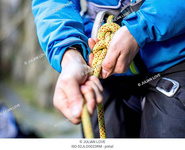 Rock climber tying rope